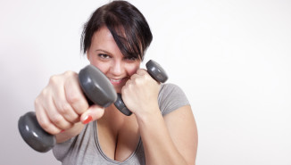 Playful overweight woman exercising, lifting weights